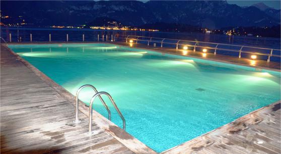 custom swimming pool design - night time lit swimming pool